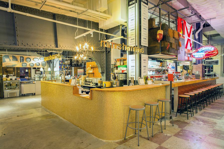Mimi's Hummus food stall with gold tile counters in Urbanspace Vanderbilt, a food hall located near Grand Central Terminal. MEP by 2L Engineering, a New York based firm.