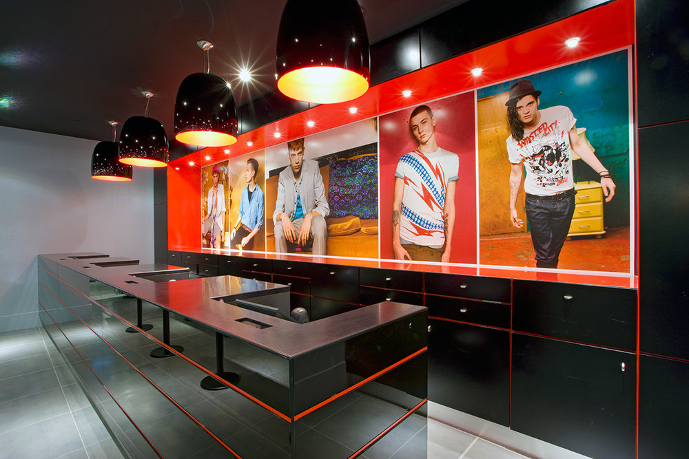 Cash registers with large posters of male models behind in the Topshop / Topman store in New York City. MEP provided by 2LS Consulting Engineering.