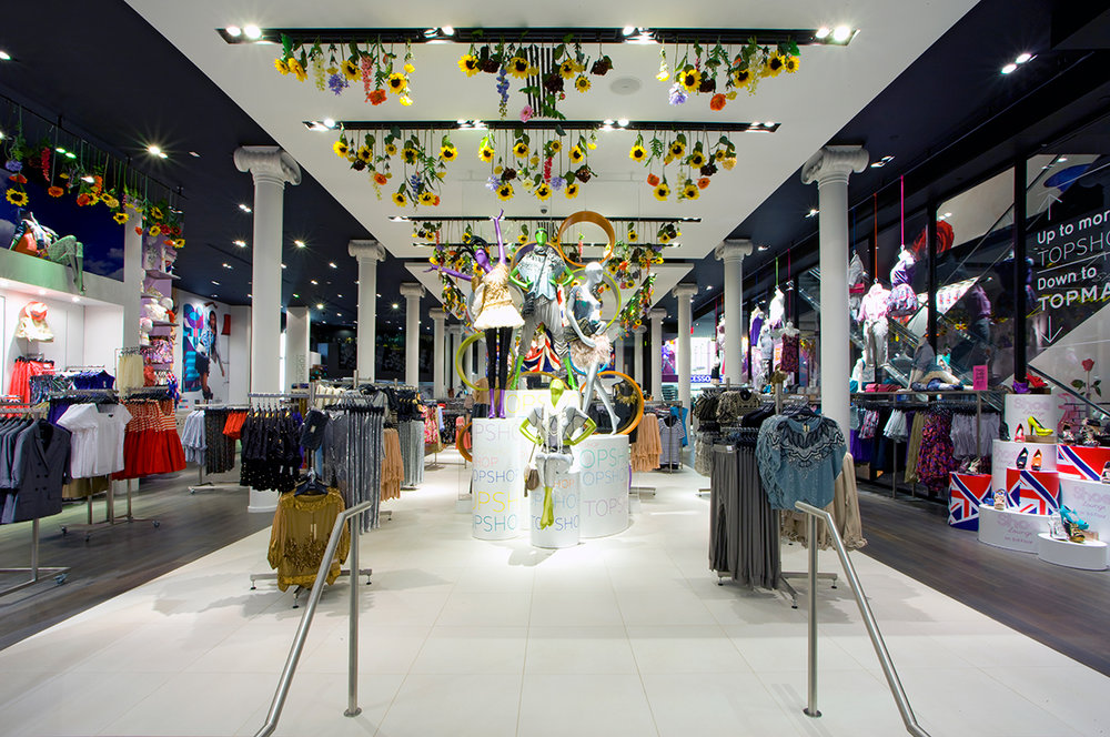 Front on perspective of the mannequin display with fun, flowery colors and decorations surrounded by various clothing racks in Topshop / Topman. MEP by New York firm 2LS Consulting Engineering.