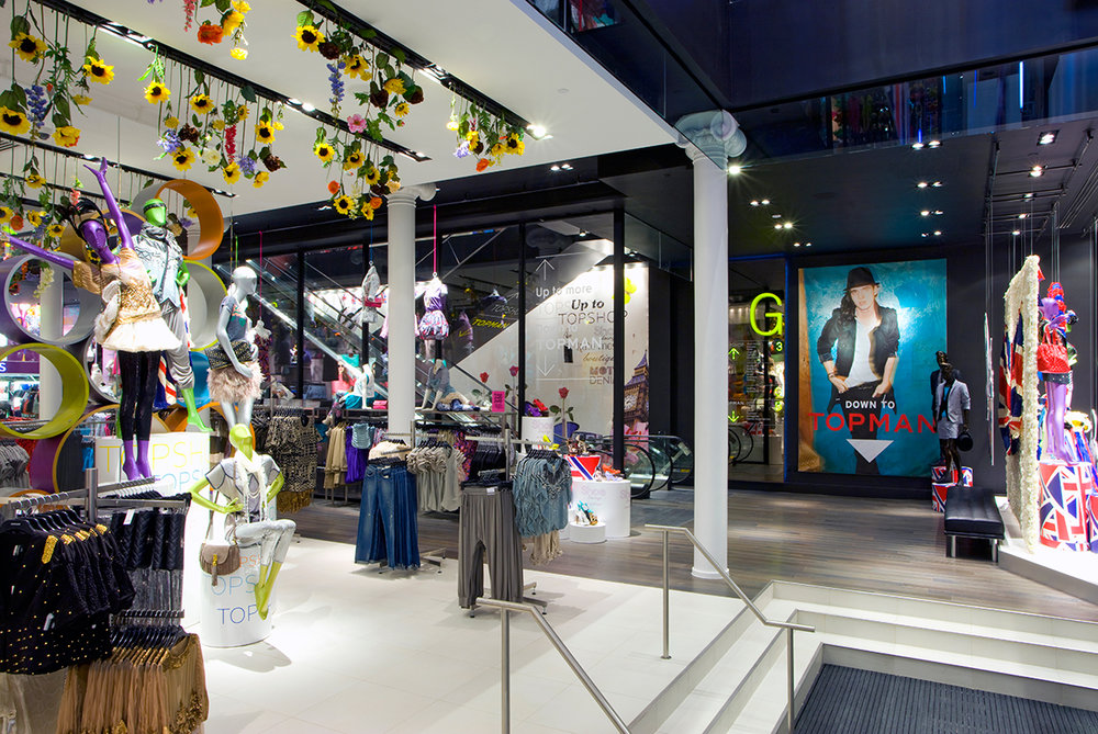 Fun, floral decor hanging from the ceiling over the women's' clothing area of Topshop / Topman in New York. MEP designed by 2L Engineering.