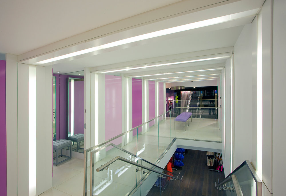 Changing rooms in white with light purple accents on a landing above a staircase in Topshop Topman, New York. MEP designed by 2L Engineering.