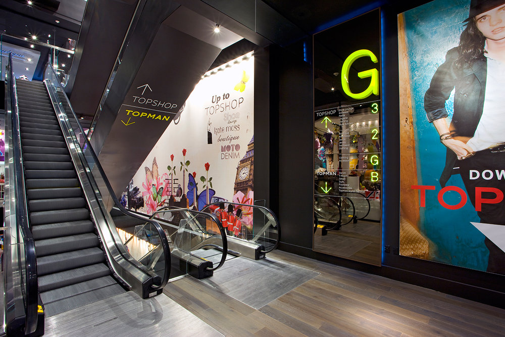 Escalators with signage directing customers to Topshop or Topman, a British retail store located in New York City. MEP provided by 2L Engineering.