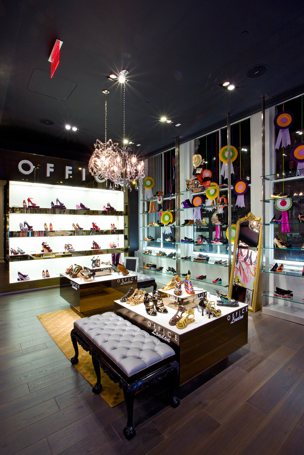 Womens sandals and heels on a brightly lit display table and shelf with chandeliers overhead. MEP designed by 2L Engineering.