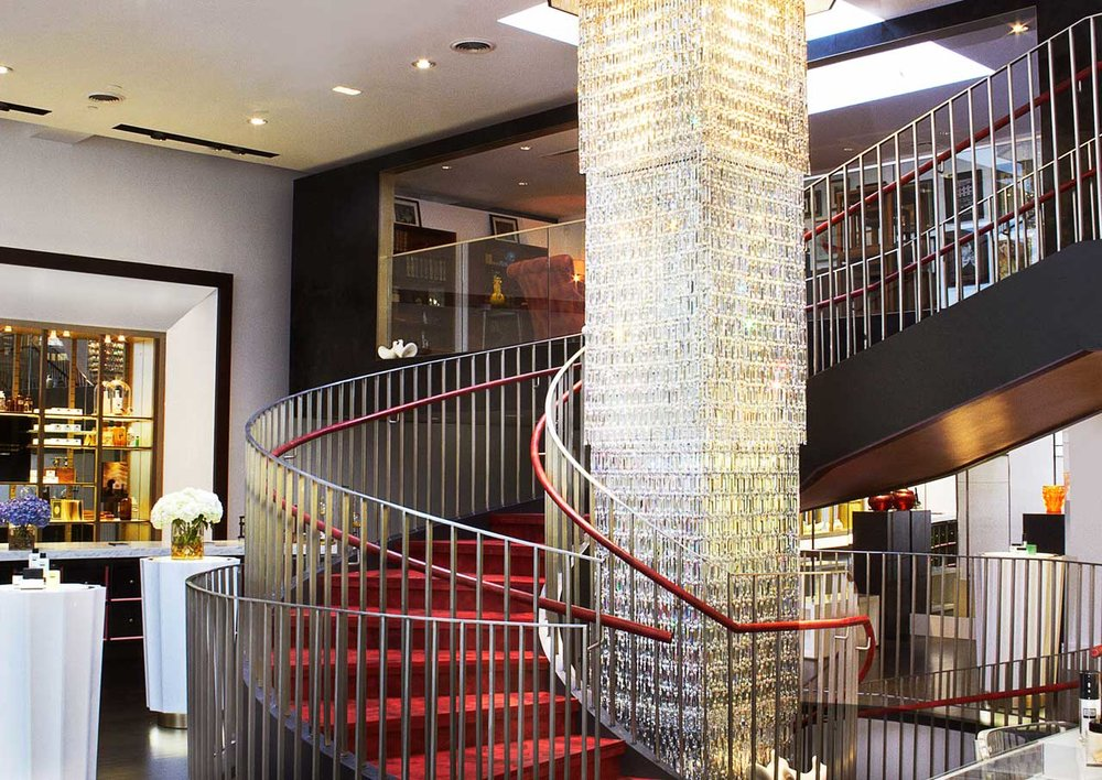 Spiral staircase with red carpeting and red handles, feauturing an ornate center in Institute Erno Laszlo Skincare, a luxury skincare retail store and spa in Soho, New York. MEP by 2LS Consulting.