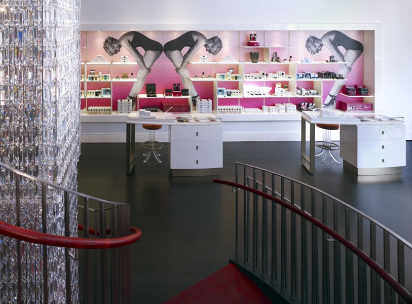 Skincare stations by display shelves for beauty products and a wallpaper featuring a vintage image of a woman in a leotard with a pink background in Institute Erno Laszlo Skincare. MEP by 2LS.