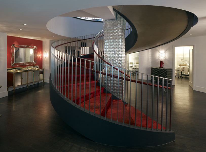Spiral staircase with red carpeting around a glass column near private spa rooms in Institute Erno Laszlo, a luxury skincare retail store and spa in Soho, New York. MEP by 2LS Consulting.