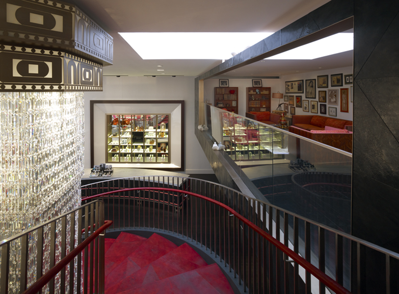 The top of the spiral stairscase overlooking an open platform seating area with red couces in Institute Erno Laszlo, a luxury skincare retail store and spa in Soho, New York. MEP by 2LS Consulting.