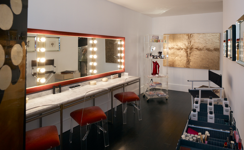 Brightly lit vanity room with different beauty and make up products in the counters and an abstract painting on the wall. MEP designed by 2LS Consulting Engineering.