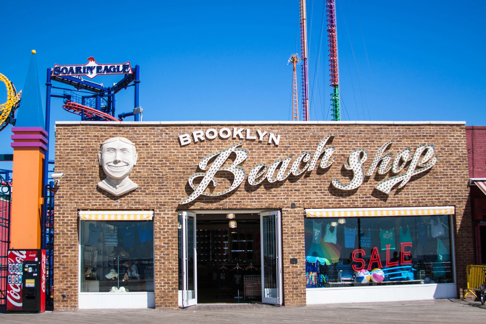 Brooklyn Beach shop exterior facade with inlaid brick and the famous Face of Steeplechase - the iconic Coney Island mascot - beside the store signage. MEP designed by 2L Engineering.