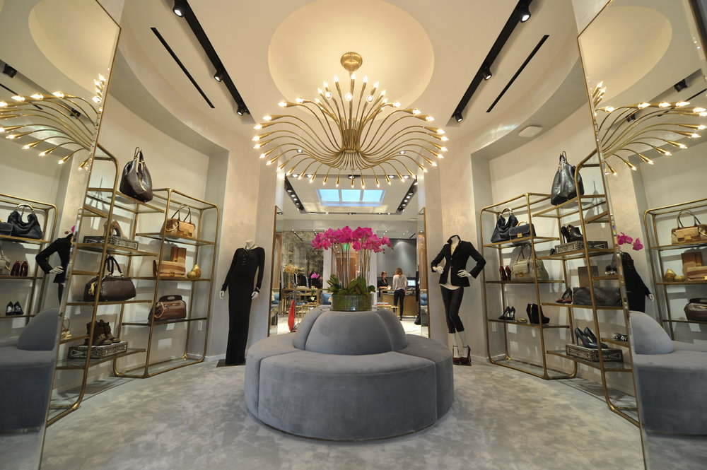 Large wiry chandelier over a grey circular couch and grey carpet surrounded by display shelves featuring handbags and shoes by Monika Chiang. MEP designed by 2LS Consulting Engineering.