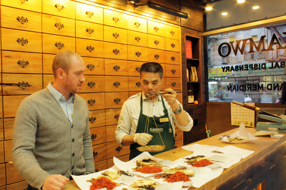 Man teaching  an employee how to weigh different medicinal herbs with various tissues holding piles of herbs at Kamwo Meridian Herbal Pharmacy in Chinatown, New York. MEP by 2L Engineering.