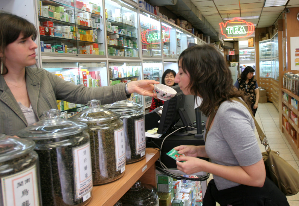 A woman holding out herbs in a bowl for a customer to smell in Kamwo Meridian Herbal Pharmacy in Chinatown. MEP designed by 2L Engineering.