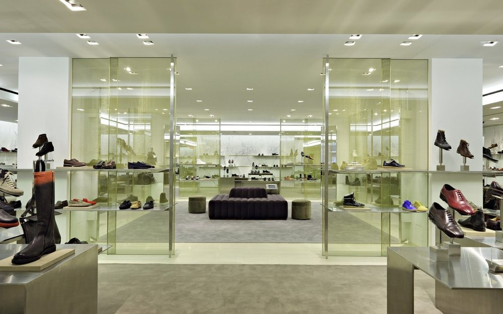 Mens shoes such as loafers, boots, and oxfords with a seating area on grey carpet in the center at Barney's New York. MEP provided by 2LS Consulting Engineering.