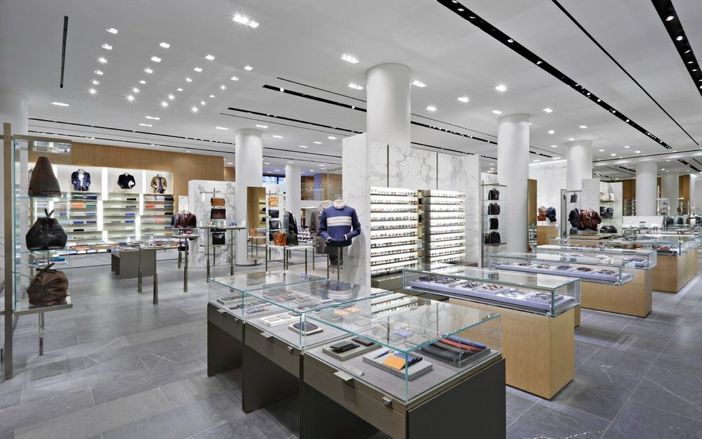 Wallet, sunglasses, and bag displays with menswear in the background at Barney's New York. MEP designed by 2LS Consulting Engineering.