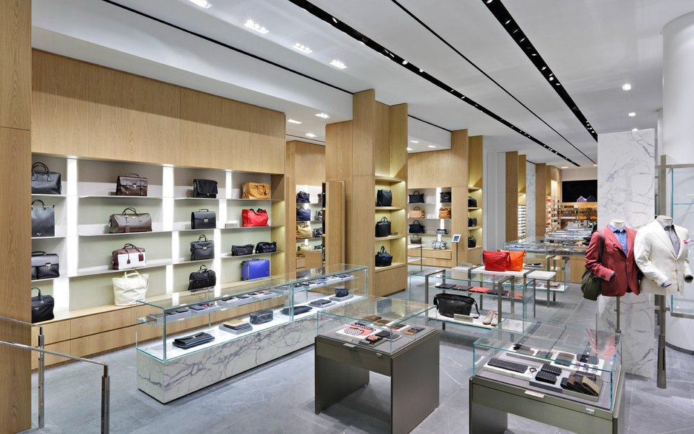 Luggage and other types of bags with well-dressed mannequins in Barney's New York. MEP designed by 2LS Consulting Engineering.