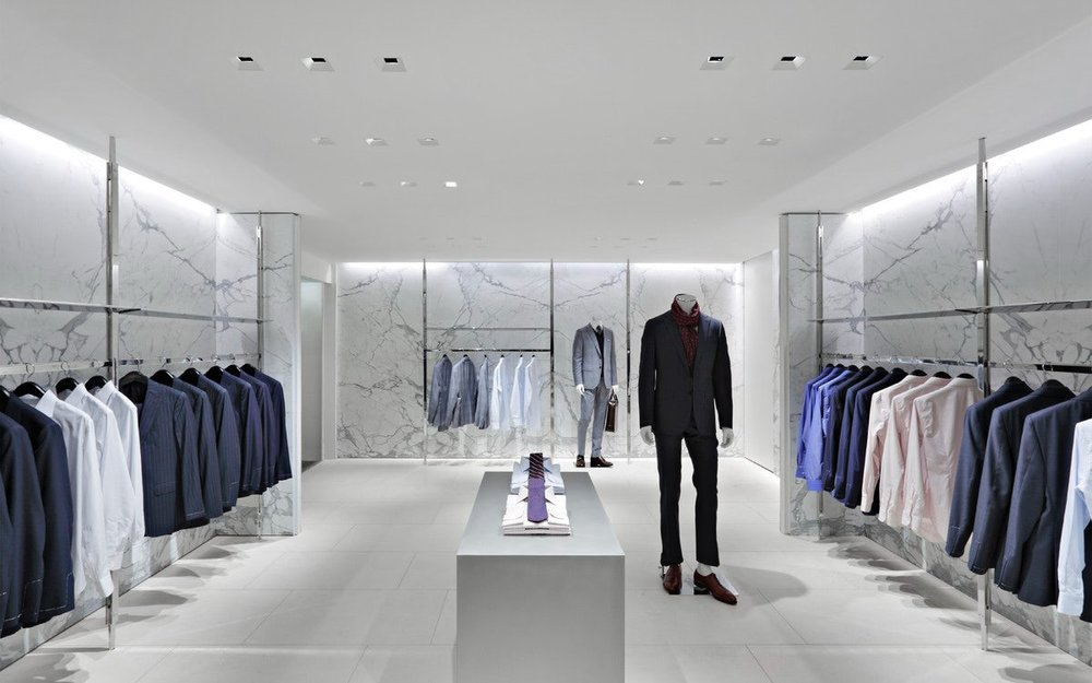 Sharply dressed mannequins in the menswear section of Barney's New York surrounded by clothing racks and a minimalistic interior. MEP designed by 2L Engineering.