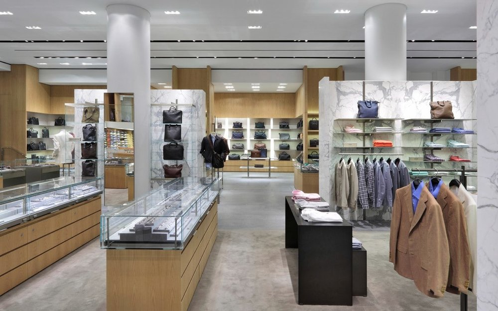 Mens accessories in display cases, bags on display shelves, and blazers for customers to browse in Barney's New York department store. MEP designed by 2L Engineering.