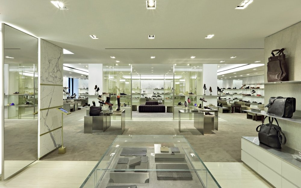 View of the mens shoewear section from mens accessories, wallets, and bags at Barney's New York. MEP provided by 2LS Consulting Engineering.