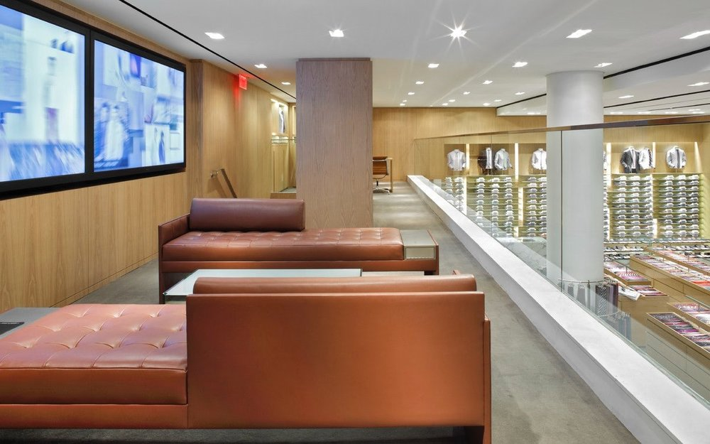 Leather brown couches in a seating area with screens showing the lastest from Barney's New York catalogue. MEP designed by 2LS Consulting Engineering.