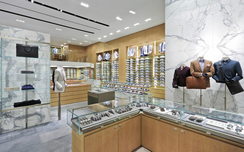 Watches in a display case with mannequins wearing smartly dressed clothes and leather goods in Barney's New York. MEP designed by 2LS Consulting Engineering.
