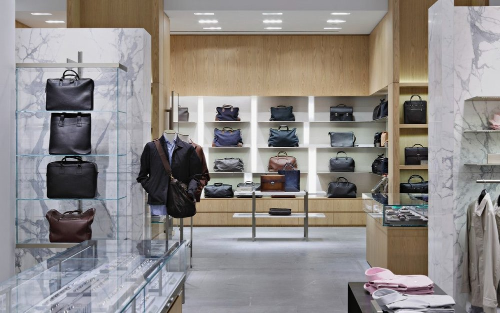 Leather goods and mens bags on display shelves at Barney's New York. MEP provided by 2L Engineering.