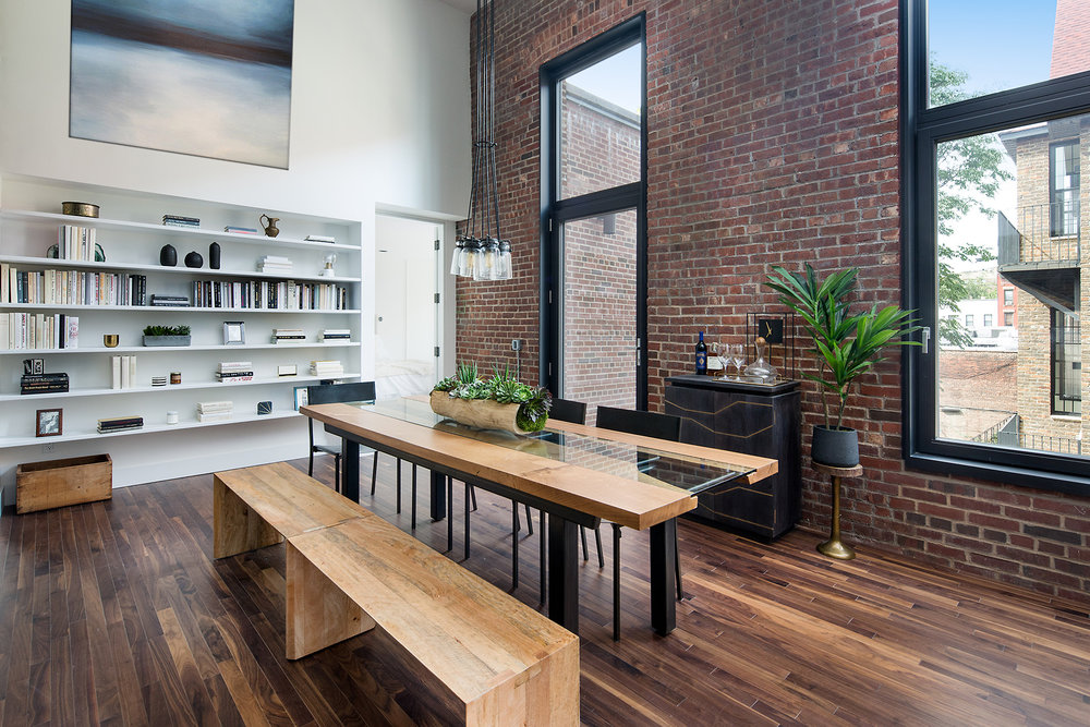 Dining area with a rustic flare mixed with modern design, a bookshelf and brick wall in a Brooklyn apartment. MEP provided by 2L Engineering.