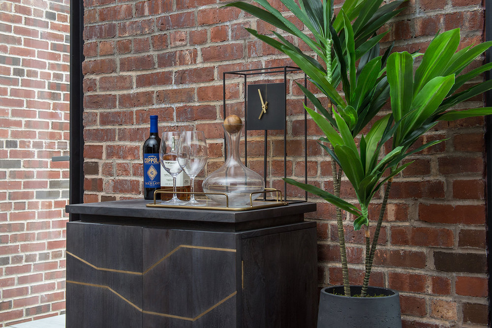 Geometric mini bar with wine, whiskey, glasses, and a minimalistic clock beside a plant against a brick wall. MEP designed by 2LS Consulting Engineering.