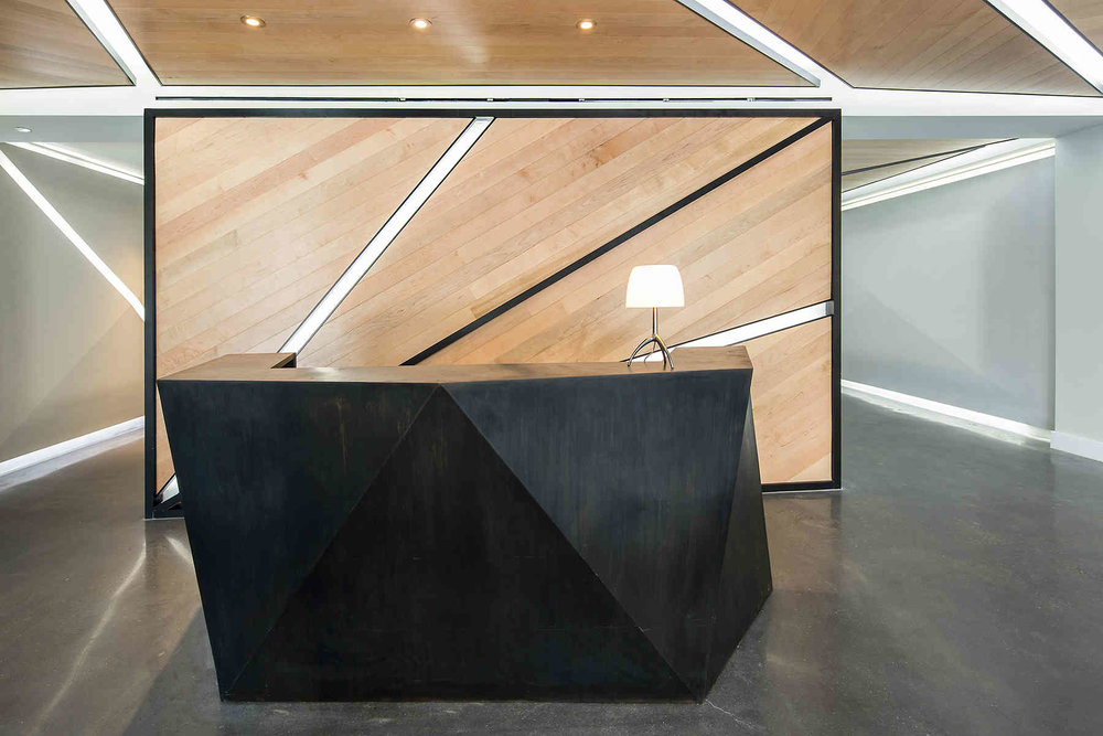 Reception area with a geometric, black desk and a modern lamp in front of a wood panel wall. MEP designed by 2LS Consulting Engineering.