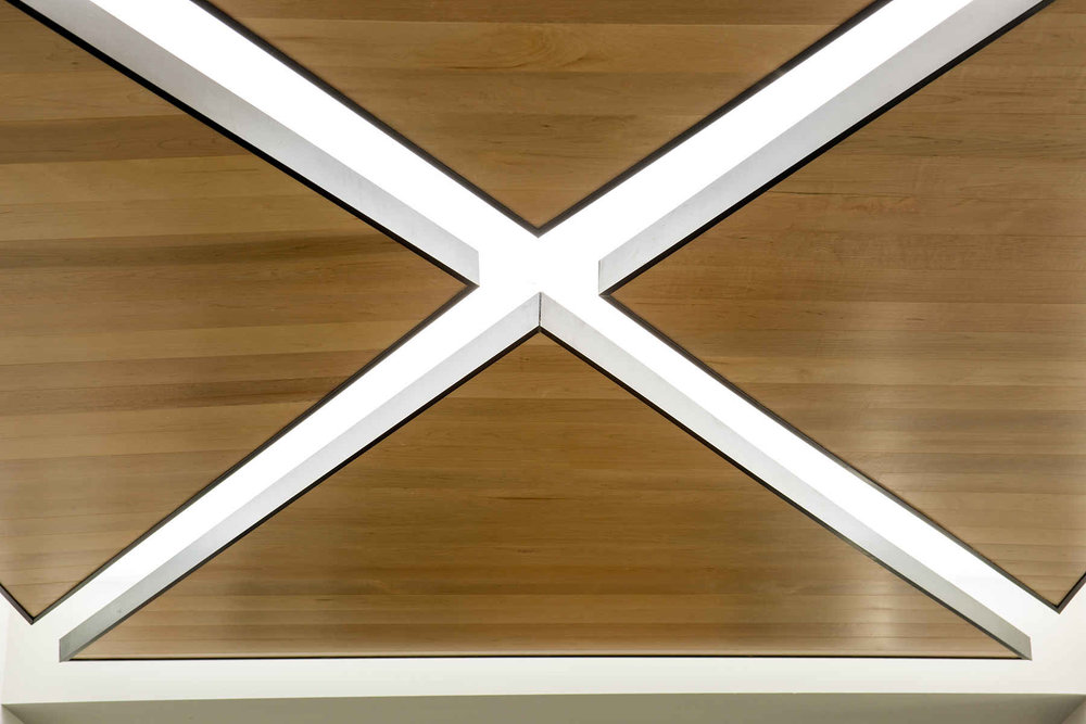 Detail shot of wood panel ceiling with light in a Brooklyn residential building. MEP designed by 2L Engineering.