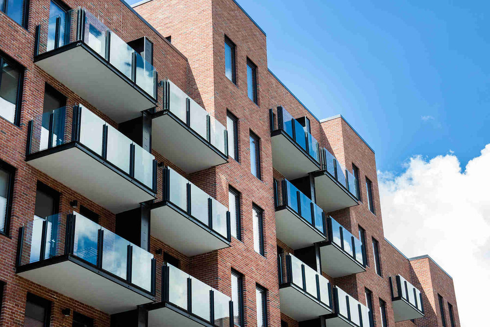 Balconies with glass railing on a residential building with a brick exterior in Brooklyn, New  York. MEP designed by 2L Engineering.