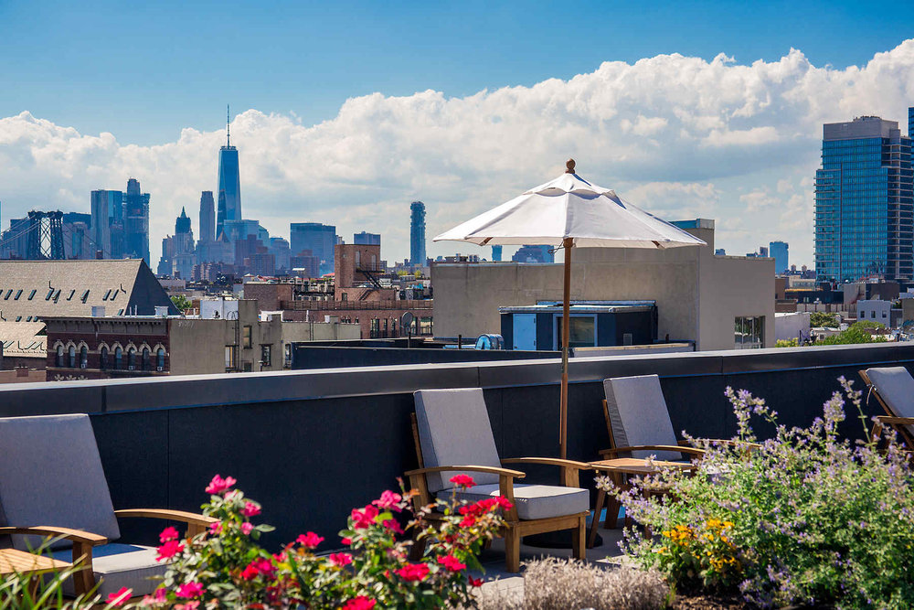 Rooftop with seating and umbrellas on a Brooklyn residential building facing the Manhattan skyline.  MEP designed by 2LS Consulting Engineering.