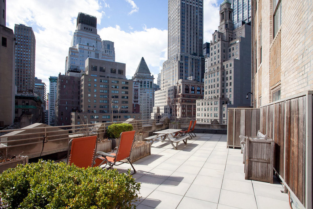 Seating area on the balcony of a luxury apartment building overlooking the New York skyline. MEP designed by 2L Engineering.