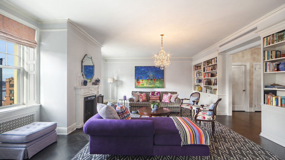 Living room with fireplace and chandelier and a large purple couch and other bohemian decor. MEP designed by 2L Engineering.