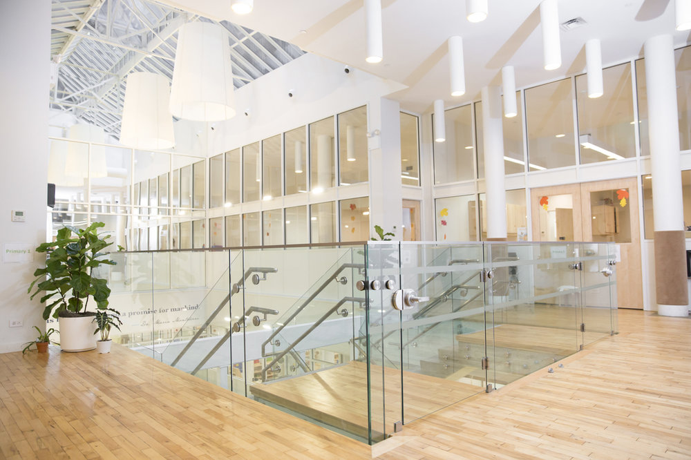 Wood and glass accented staircase in the Flatiron location of the Montessori School in New York City. MEP provided by 2LS Consulting Engineering Firm.