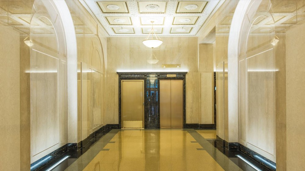 Gold elevators in a brightly lit lobby featuring a chandelier and delicate, flowery ceiling moldings. MEP design provided by 2L Engineering.