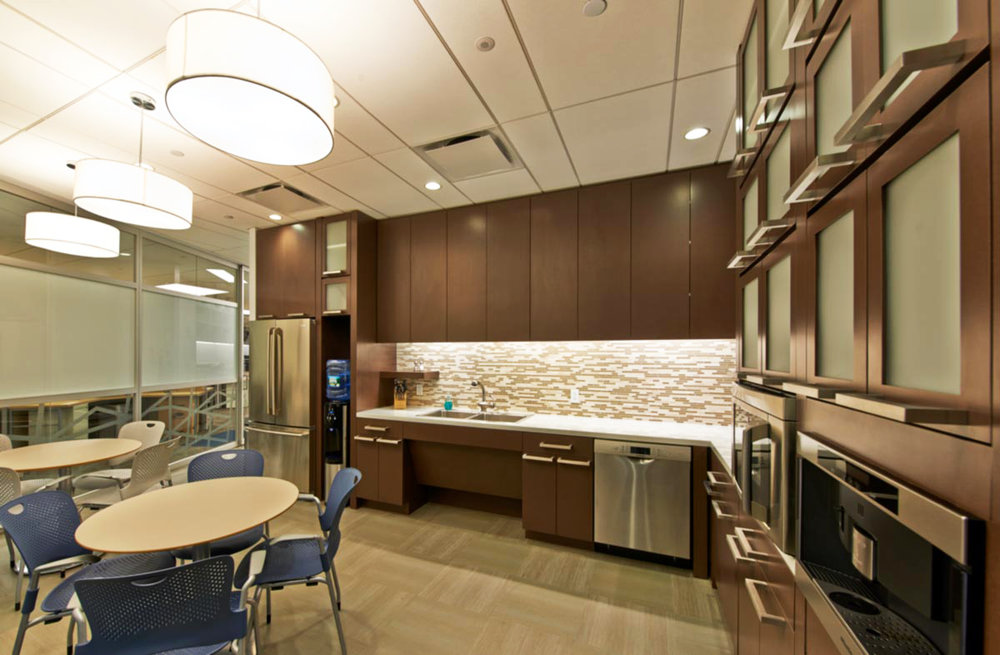 Kitchen and break room area with circular lighting and abundant storage space in the offices of Wood Mackenzie in New York. MEP designs by 2LS Consulting Engineering.