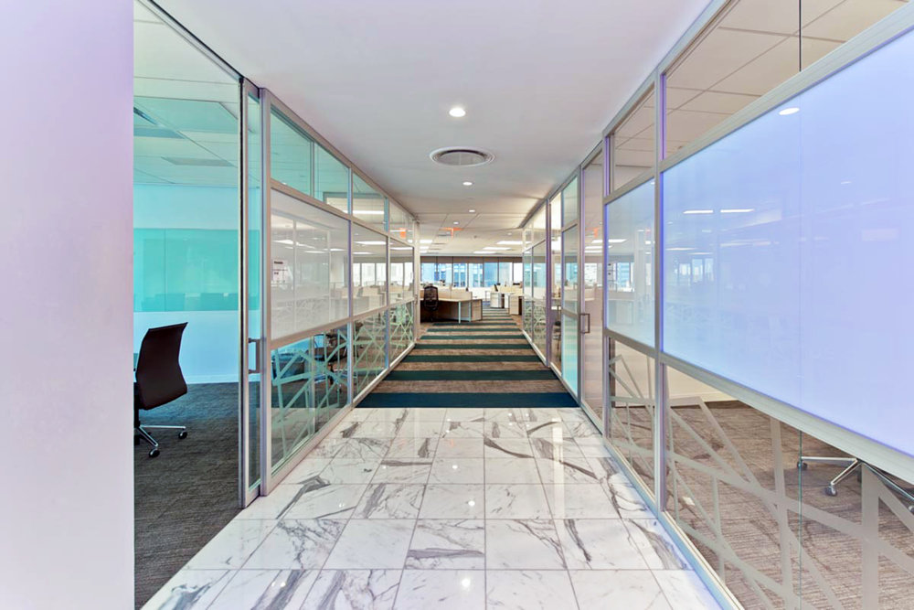 Blue tinted private conference rooms with marble flooring and striped carpeting in the offices of Wood Mackenzie in New York. MEP designed by 2L Engineering.