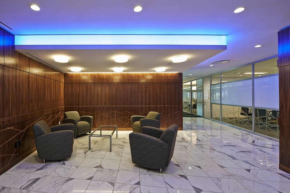Lounge area with geometric designs on the wooden wall pannels and blue mood lighting at the offices of Wood Mackenzie in New York. MEP designs by 2LS Consulting Engineering.
