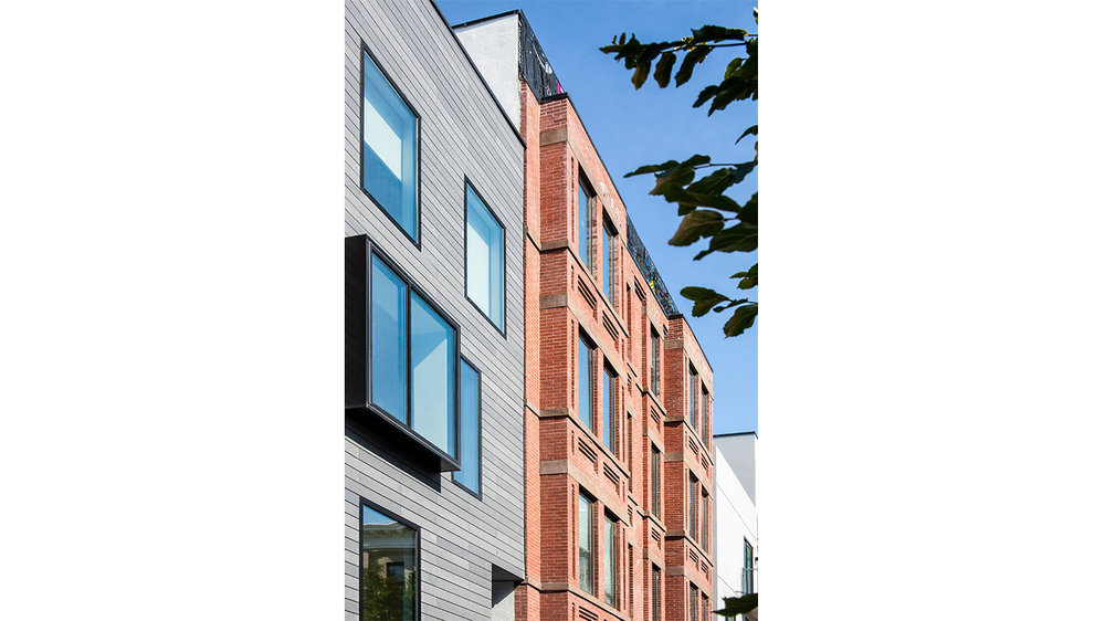 Brick and wood facade of a residential building in Brooklyn facing the sidewalk. MEP provided by 2LS Consulting Engineering.