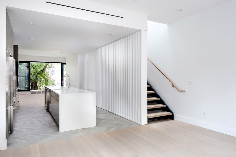 Porous wall partition separating stairs and an open kitchen plan with an island and chevron tiling. MEP design provided by 2L Engineering.