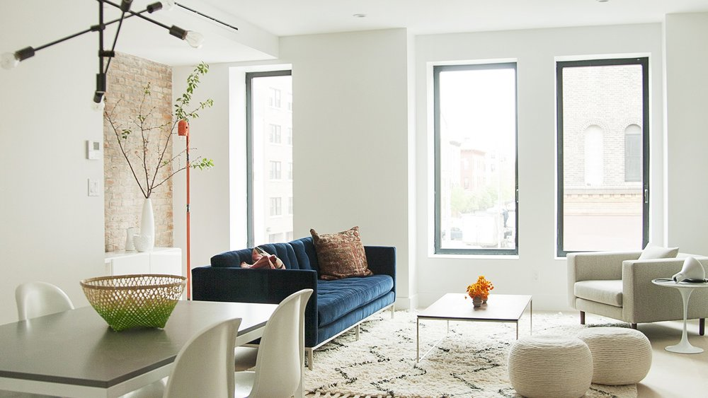 Large windows looking into a Scandinavian style living room with a big navy blue couch in a luxury residential home in Brooklyn. MEP by 2LS Consulting.