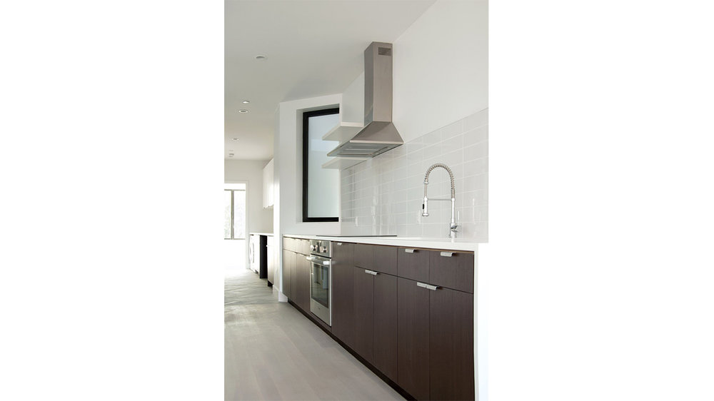Luxury kitchen with a minimalistic design and dark wood cabinets. MEP provided by 2L Engineering.