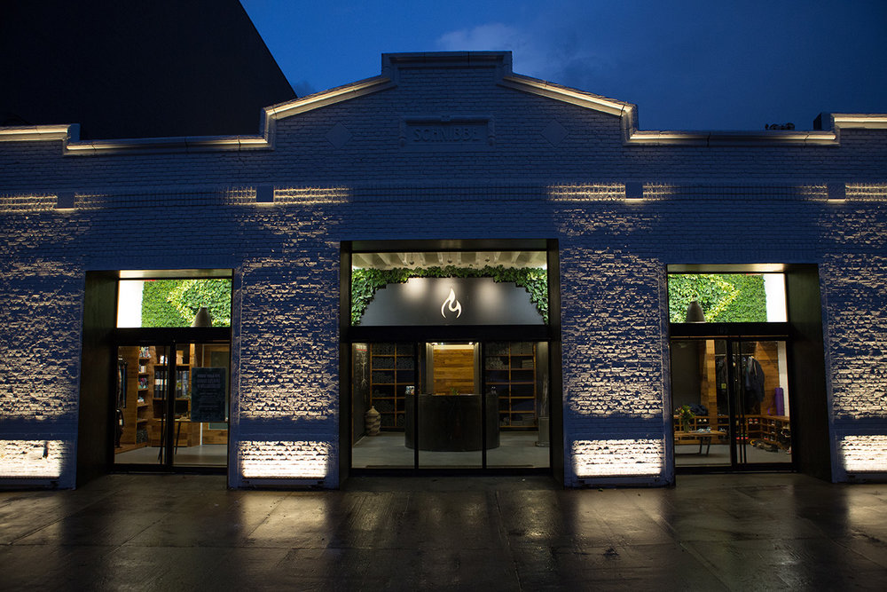 Light brick exterior of Modo Yoga with the brand's logo illuminated inside on a rainy evening in Brooklyn, New York. MEP designed by 2LS Consulting Engineering.