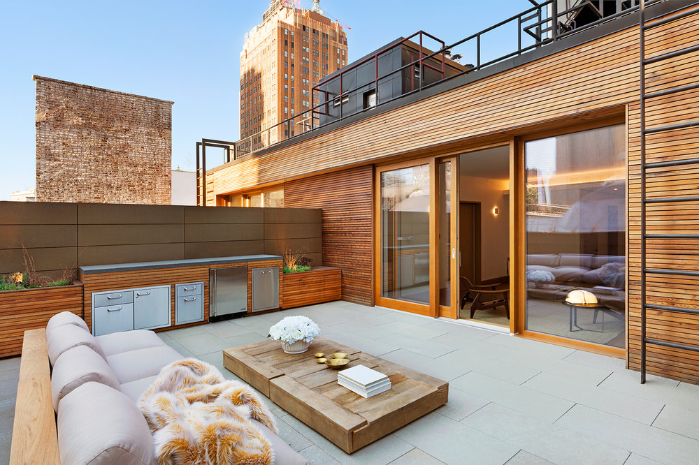 Lounge area with wood accents on the rooftop of a luxury residential building. MEP designed by 2L Engineering.