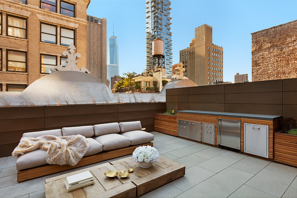 Lounge area with bar, sofa, and coffee table on the rooftop of a luxury residential building surrounded by New York skyscrapers. MEP designed by 2L Engineering.