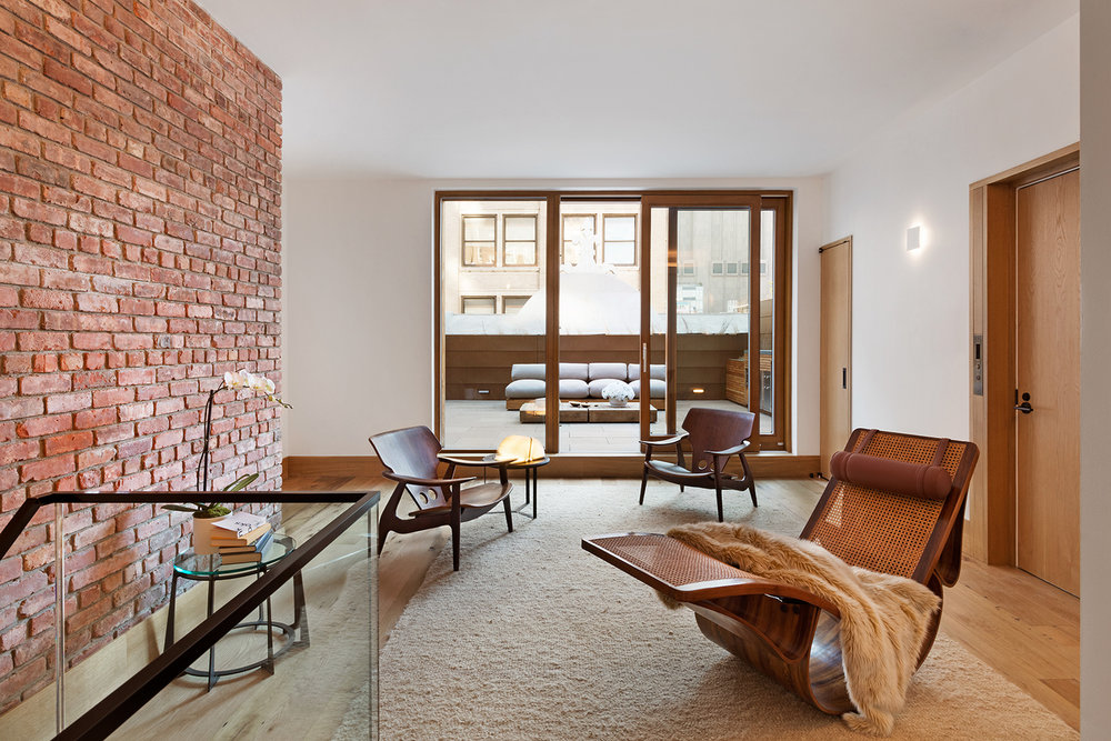 Sitting space with a modern rocking chair beside the stairs, elevator, and facing the doors leading to a private rooftop. MEP by 2L Engineering..