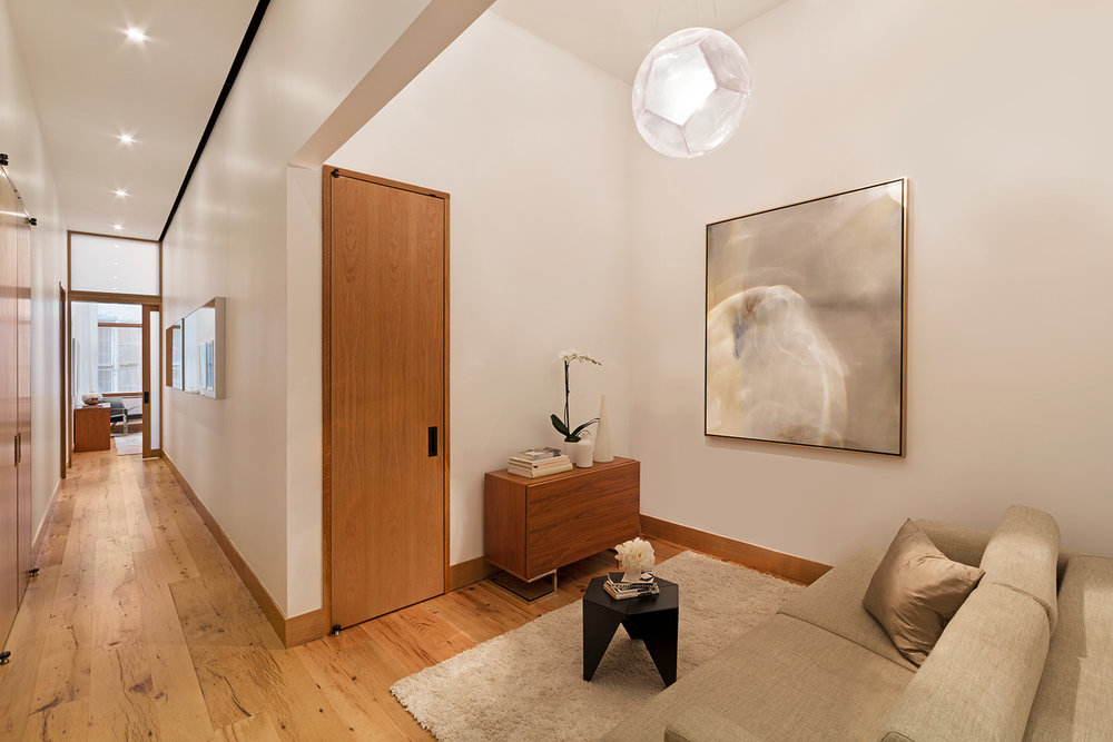 Private sitting area with abstract art and a storage closet beside a hallway in a luxury apartment. MEP designed by 2L Engineering.
