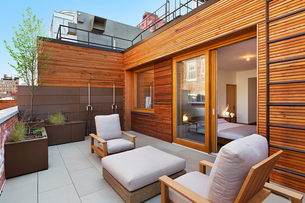 Outdoor lounge area beside doors leading to a bedroom, featuring wood panelled walls. MEP designed by 2L Engineering.