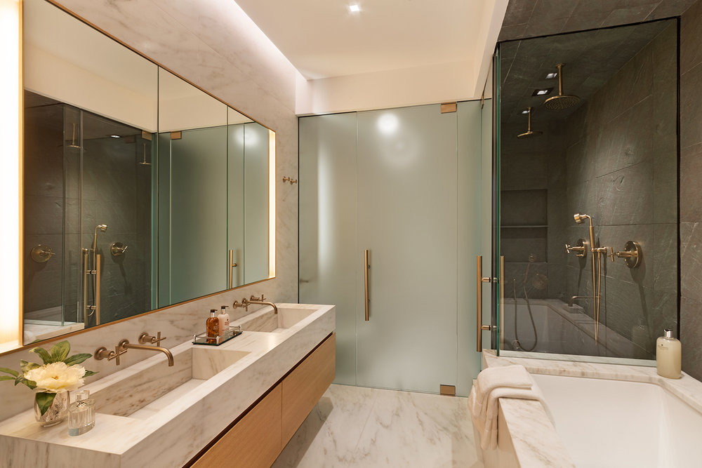 Luxury bathroom with separate shower and bathtub, his and hers sinks, along with marble and wood accents. MEP designed by 2L Engineering.