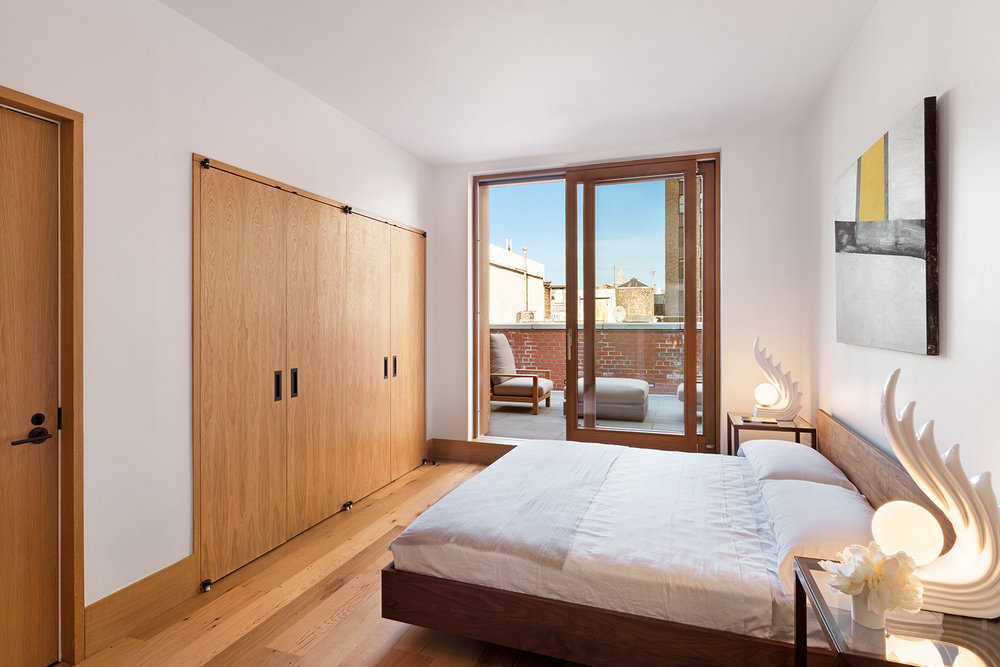 Bedroom with ample closet space and its own access to a private balcony space. MEP designed by 2L Engineering.